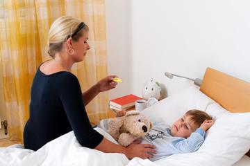 Mutter und krankes Kind im Bett. Grippe. Kinderkrankheiten.