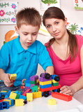 Child playing  lego  block with mother at home. poster