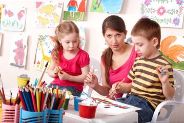 Children  painting with teacher in school.