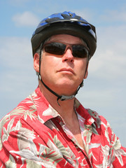Smiling man in red shirt and blue bicycle helmet