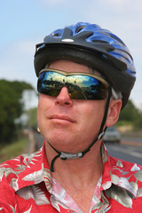 Smiling bicyclist in red shirt and blue helmet