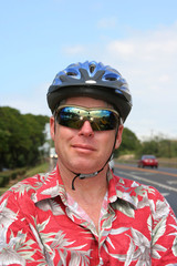Smiling man in red shirt and bicycle helmet