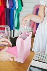 Caucasian saleswoman giving a shopping bag to a customer