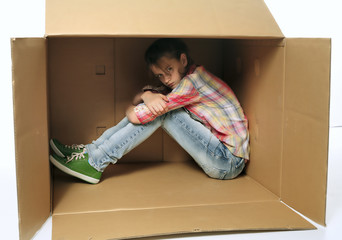 Angry teenage girl siting in box and irritating - bad mood