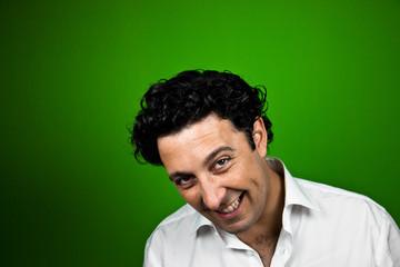 Hombre picaro sonriendo a camara sobre fondo verde