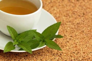 Cup of herbal tea and  mint leaves