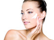 woman applying moisturizer cream on cheek