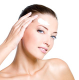 woman applying moisturizer cream on forehead poster