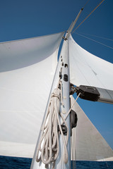 Yacht sail and mast with blue cloudless sky in the background