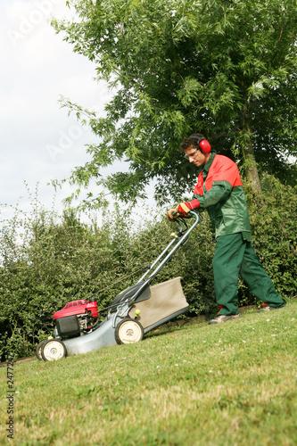 Un jardinier paysagiste tond le gazon avec tondeuse for Tarif tondeuse a gazon