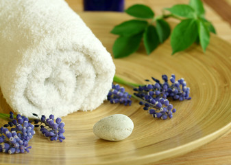 spa composition of towel, flowers and stone