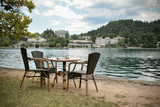 Bar table and chairs near the lake poster