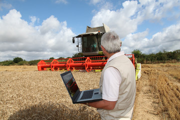 Man in front of harvesting machine in wheat field