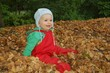 Autumn_cute child sitting within leaves