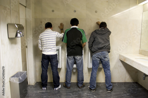 three men stading up, peeing in the bathroom