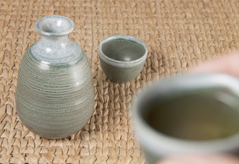 A green pottery tea set with one cup raised to drink