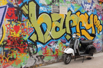 Single moped in front of Graffiti