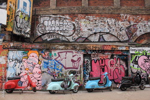 Four mopeds in front of graffiti