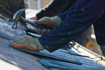 Roofer hammering close up