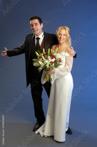 Portrait of the young happy newlyweds on dark background