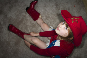Young girl dressed up in cowgirl outfit.