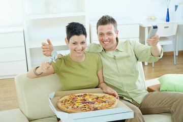 Happy couple eating pizza