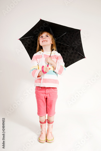 beautiful young girl holding umbrella and looking up smiling