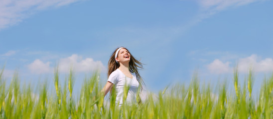 happy girl in green grass over sky background