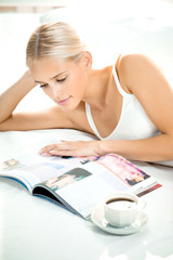 Young woman reading a magazine at bedroom