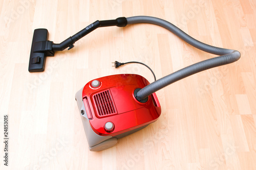 Vacuum cleaner on the wooden floor