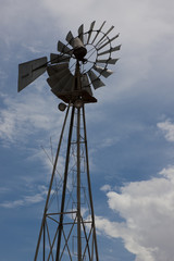 Rural Windmill Backlit Against Partly Cloudy Sky