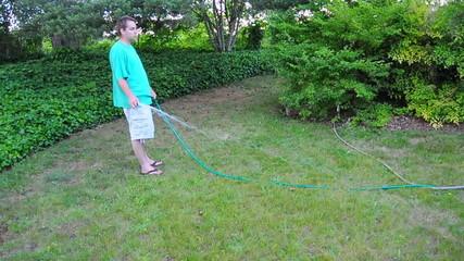 Man Waters the Grass Lawn Yard