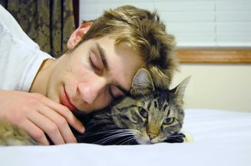 Young man sleeps on his bed using his cat as a snuggle pillow.