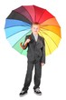 boy wearing suit is standing with umbrella. isolated.