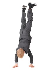 boy wearing suit and sneakers doing handstand. isolated.