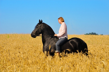 Beautiful woman rides horse in field