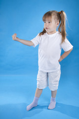 Small serious girl is posing isolated on blue