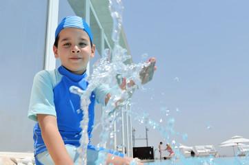 Cute boy splashing water on camera.