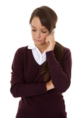 Worried schoolgirl using mobile phone