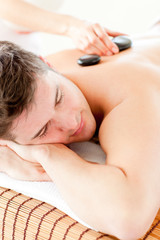 Attractive man enjoying a massage with hot stone