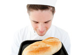 Handsome male cook smell at a fresh bread