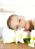 Fototapety Portrait of a charming woman lying on a massage table smiling at