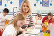 Group Of Primary Schoolchildren And Teacher Having lesson In Cla