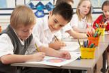 Group Of Primary Schoolchildren In Classroom Working At Desks poster