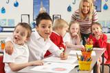 Group Of Primary Schoolchildren And Teacher Working At Desks In poster