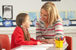Female Primary School Pupil And Teacher Working At Desk In Class