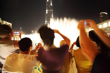 tourists in Dubai recording video and taking photos at night