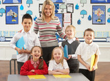 Portrait Of Group Of Primary Schoolchildren And Teacher Sitting poster