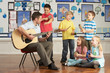 Male Teacher Playing Guitar With Pupils Having Music Lesson In C