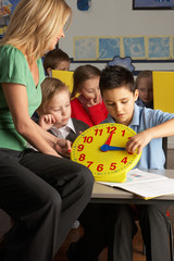 Female Teacher In Primary School Teaching Children To Tell Time
